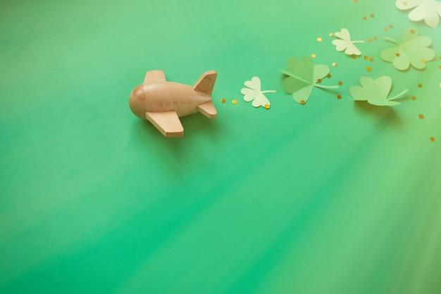 Dia de são patrício, trevo de sorte avião sobre um fundo verde Foto Premium