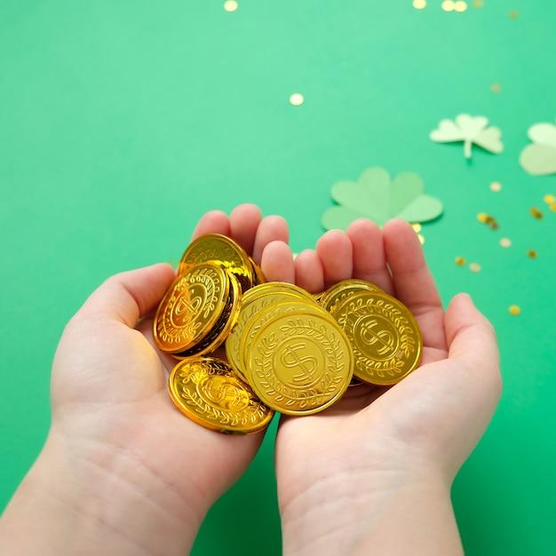 Dia de são patrício, trevo e moedas de ouro sobre fundo verde Foto Premium
