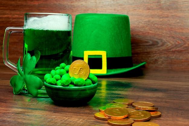 Dia de são patrick. caneca de vidro verde de cerveja, doces de biscoitos de petiscos verdes, chapéu verde de duende, trevo de três pétalas verde e moedas de ouro na mesa de madeira Foto Premium