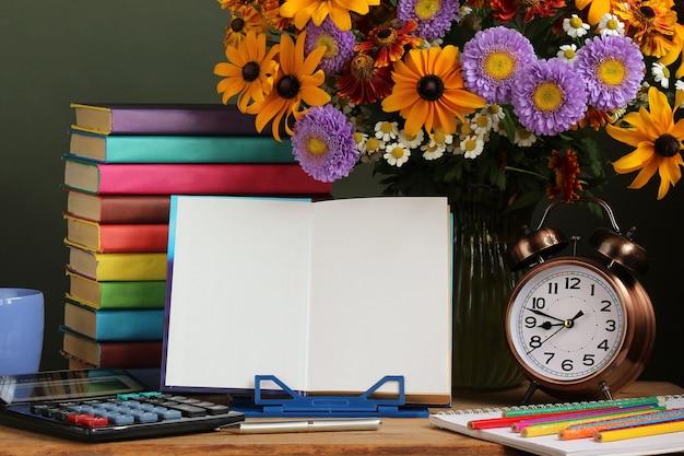 Dia do professor, 1º de setembro. de volta à escola. um buquê de flores de outono, um despertador e um livro aberto em um carrinho. Foto Premium