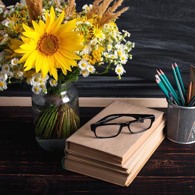 Dia do professor. placa de giz preto e flores silvestres frescas em vaso Foto Premium