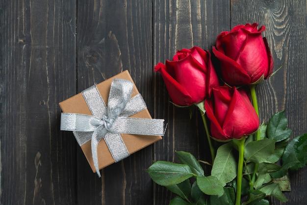 Dia dos namorados. buquê de flores rosas vermelhas e caixa de presente na mesa de madeira. Foto Premium