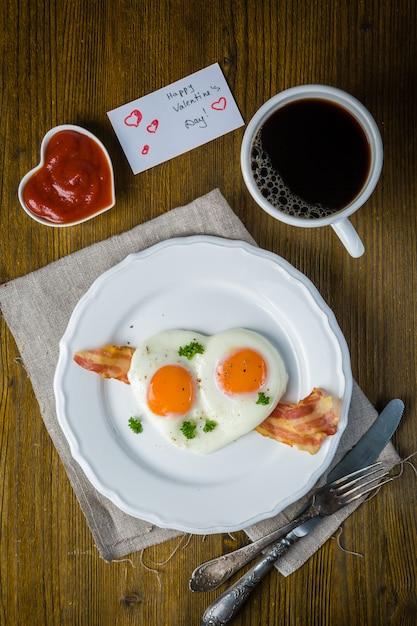 Dia dos namorados café da manhã - ovos, bacon, ketchup Foto Premium