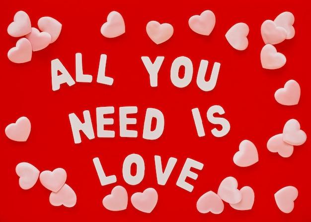 Dia dos namorados com fundo vermelho com corações rosa e a frase all you need is love forrado com letras de madeira brancas. dia das mães, cartão de 8 de março Foto Premium
