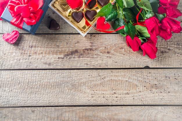 Dia dos namorados com rosas vermelhas e coração de chocolate Foto Premium