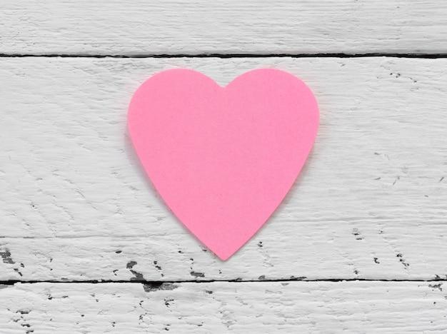 Dia dos namorados - coração rosa de papel contra uma superfície pintada de branca. Foto Premium