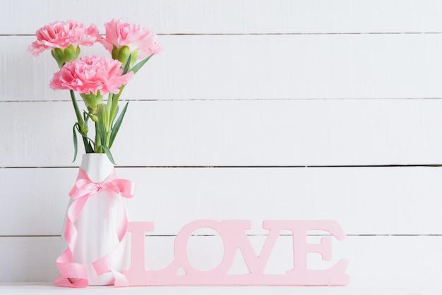 Dia dos namorados e conceito de amor. cravo cor-de-rosa no vaso no fundo de madeira. Foto Premium