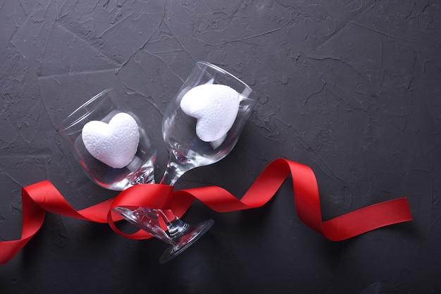 Dia dos namorados fundo cartão amor símbolos, decoração vermelha com óculos em fundo de pedra. vista superior com cópia espaço e texto. Foto Premium