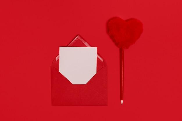 Dia dos namorados. modelo em branco para cartas românticas em um envelope em um espaço vermelho. caneta em forma de coração vermelho fofo. lei plana. vista de cima. Foto Premium