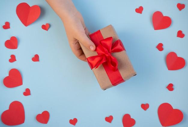 Dia dos namorados. presente na mão, uma declaração de amor, uma caixa com uma fita vermelha. vista do topo Foto Premium