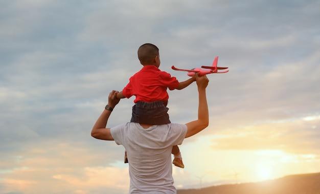Dia dos pais. pai e filho brincando juntos ao ar livre avião de papel Foto Premium