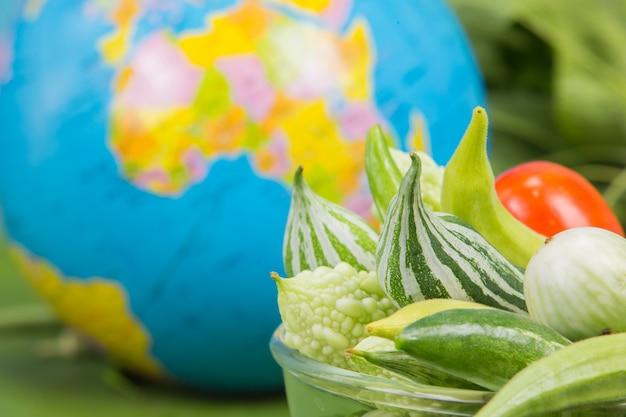 Dia mundial da alimentação, muitos vegetais estão em uma tigela com globos colocados perto das folhas de bananeira verde. Foto gratuita