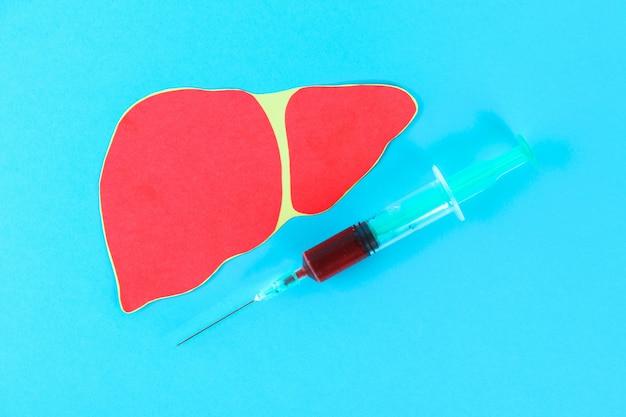 Dia mundial da hepatite. 28 de junho. uma seringa com sangue e um fígado em uma mesa azul Foto Premium
