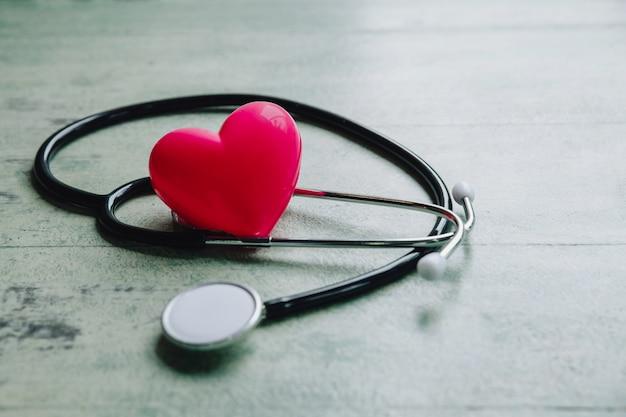 Dia mundial da saúde, coração vermelho e estetoscópio na mesa de madeira velha Foto Premium