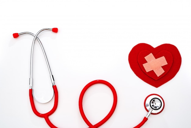 Dia mundial da saúde, cuidados de saúde e conceito médico, estetoscópio vermelho e coração vermelho sobre fundo branco Foto Premium