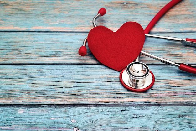 Dia mundial da saúde, cuidados de saúde e conceito médico, estetoscópio vermelho e coração vermelho sobre o fundo azul de madeira Foto Premium