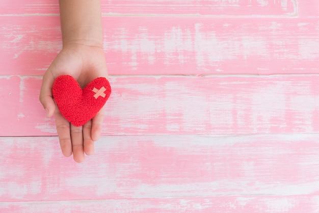 Dia mundial da saúde, mão de criança segurando artesanal coração vermelho no fundo rosa de madeira Foto Premium