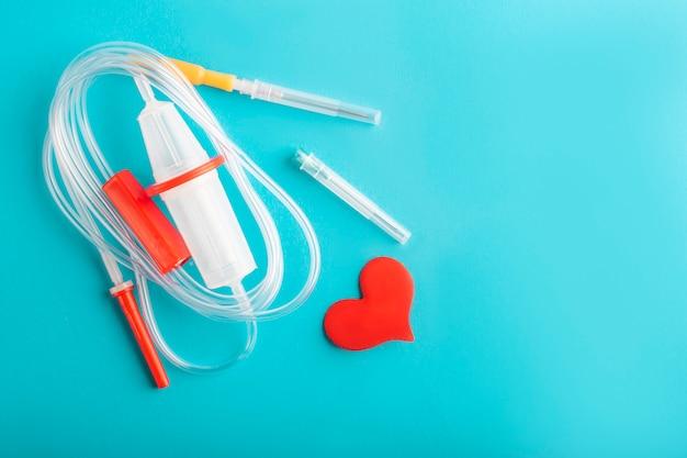 Dia mundial do dador de sangue. sistema de transfusão de sangue e coração vermelho Foto Premium
