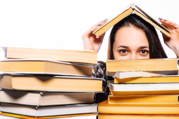 Dia mundial do livro e direitos autorais. a mulher está se escondendo atrás de livros. Foto Premium