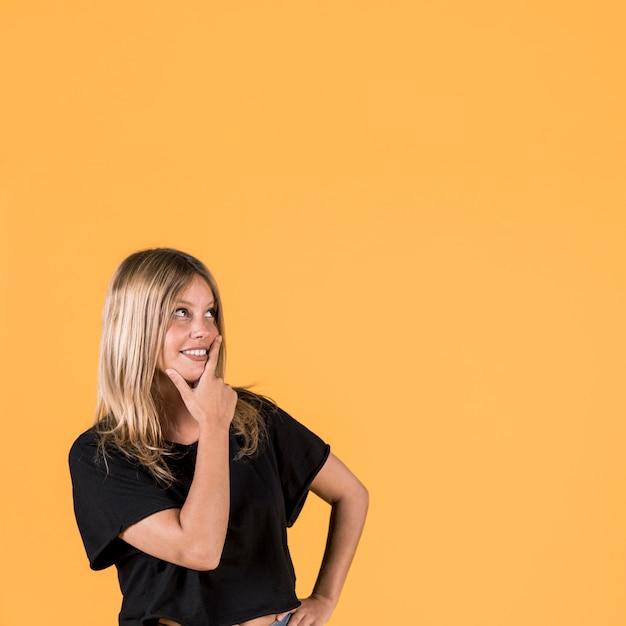 Dia sonhando sorridente jovem em pé sobre o pano de fundo amarelo Foto gratuita
