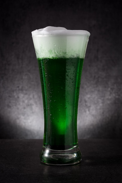 Dia tradicional st patrick verde cerveja na mesa preta. Foto Premium