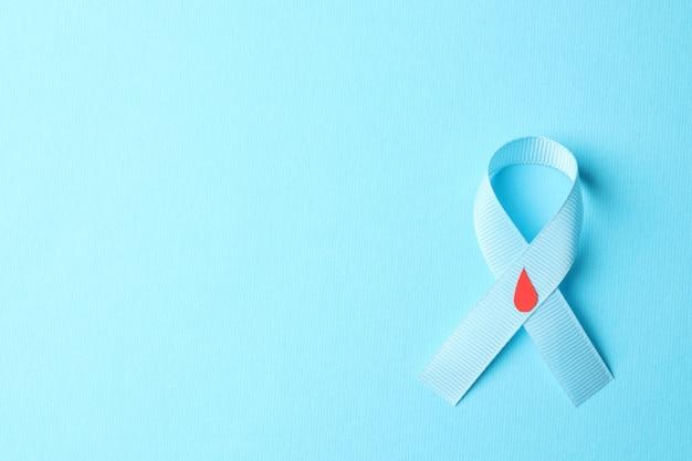 Diabetes. fita azul com gota de sangue decorada em fundo azul Foto Premium