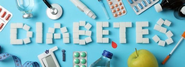 Diabetes palavra feito de cubos de açúcar sobre fundo azul. acessórios para diabetes Foto Premium