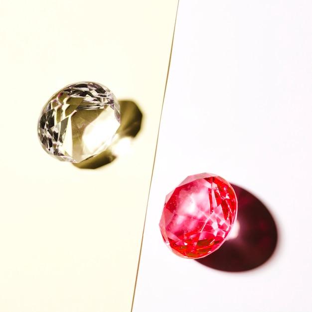 Diamante branco e vermelho caro em pano de fundo branco e bege Foto gratuita