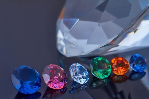 Diamante enorme e vários cristais chiques em uma superfície espelhada preta brilhante, brilho e brilho Foto Premium