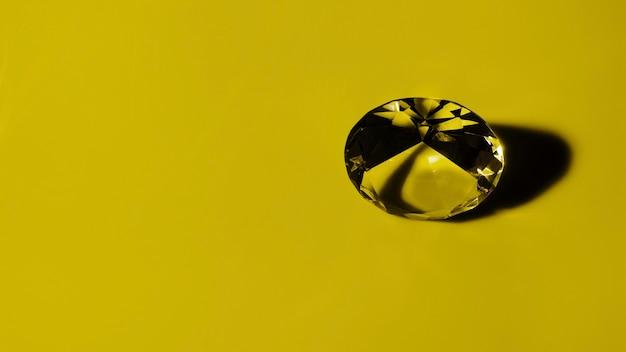 Diamante redondo transparente no fundo ocre Foto Premium