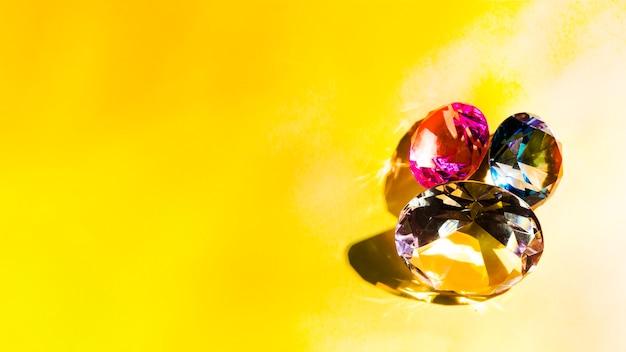 Diamantes espumantes em fundo amarelo Foto gratuita