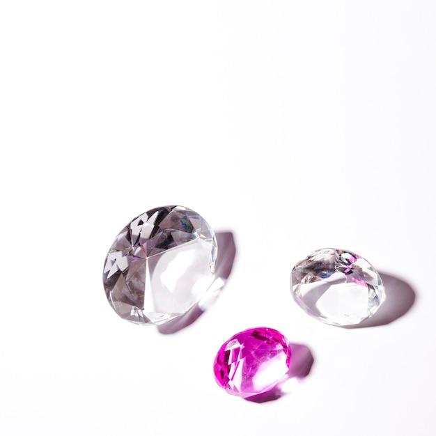 Diamantes transparentes brancos e rosa em fundo branco Foto gratuita