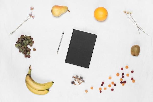 Diário de capa preta fechada e caneta com muitas frutas em pano de fundo branco Foto gratuita