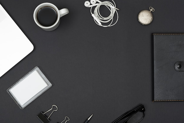 Diário; fone de ouvido; xícara de café; computador portátil; clipes de papel; óculos no desktop preto Foto gratuita