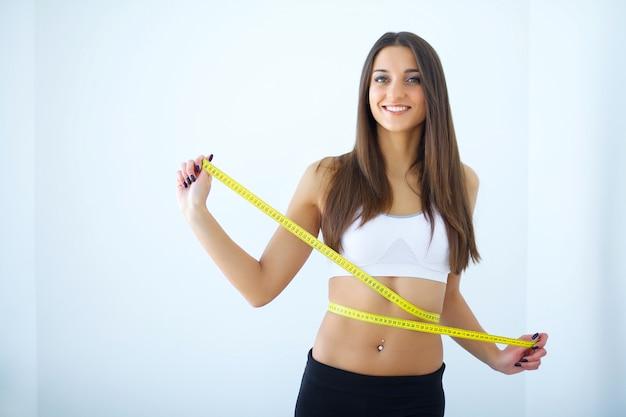 Dieta. a garota tomando medidas de seu corpo Foto Premium
