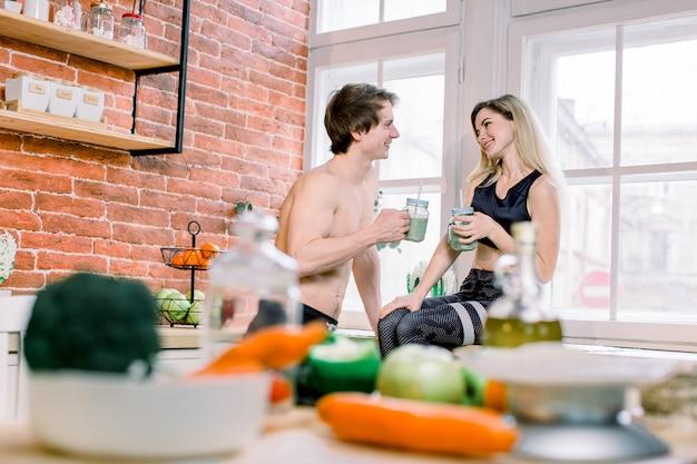 Dieta, alimentação saudável, estilo de vida fitness, nutrição adequada. casal consciente de saúde bebendo suco fresco na cozinha de casa. Foto Premium