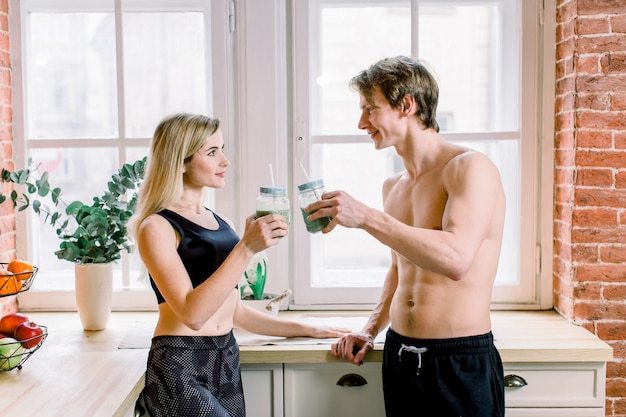 Dieta, alimentação saudável, estilo de vida fitness, nutrição adequada. jovem casal de vegetarianos bebendo suco fresco na cozinha em casa Foto Premium