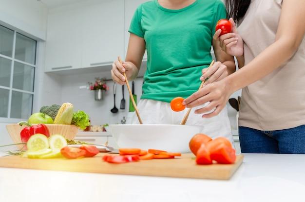 Dieta. dois, jovem, bonito, mulher, em, camisa verde, ficar, e, preparar, a, legumes, salada Foto Premium