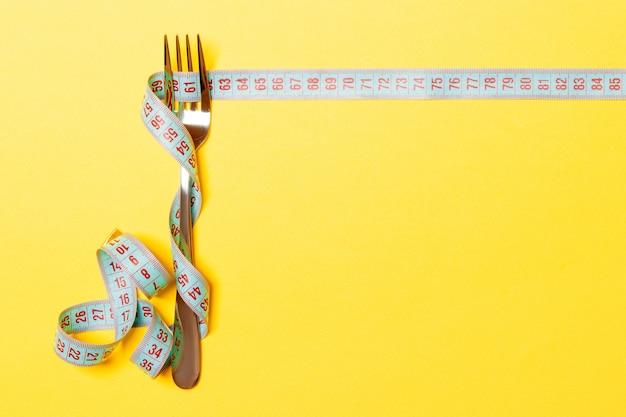 Dieta e alimentação saudável. garfo e fita métrica em fundo amarelo. Foto Premium