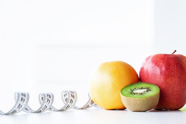Dieta. fitness e conceito de dieta alimentar saudável. dieta balanceada com legumes. vegetais verdes frescos, fita métrica. fechar-se Foto Premium