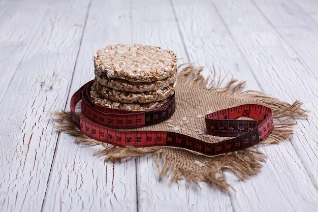 Dieta padaria de arroz e medida de fita vermelha mentira sobre a mesa de madeira branca Foto gratuita