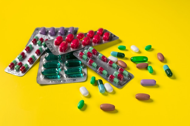 Diferentes bolhas com vários comprimidos e cápsulas e comprimidos espalhados nas proximidades, deitado sobre uma parede amarela. Foto Premium