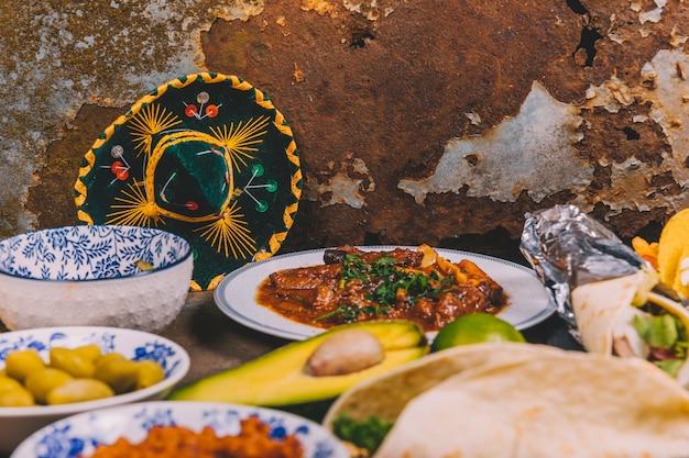 Diferentes deliciosos pratos mexicanos sobre fundo enferrujado com chapéu mexicano Foto gratuita