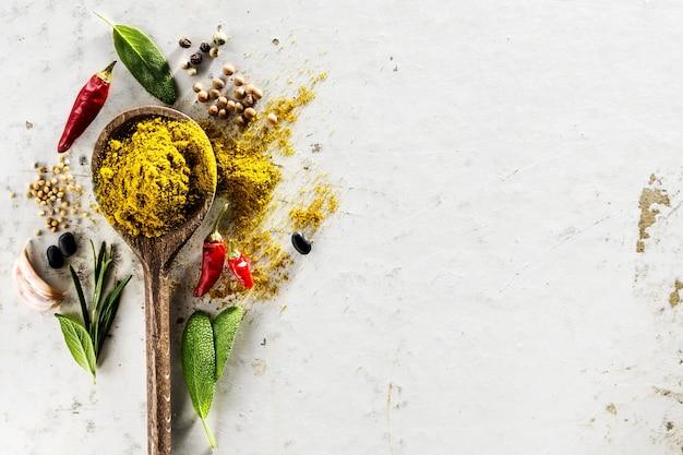 Diferentes especiarias Ingredientes alimentícios Colher de madeira no fundo do WhiteTable Foto gratuita