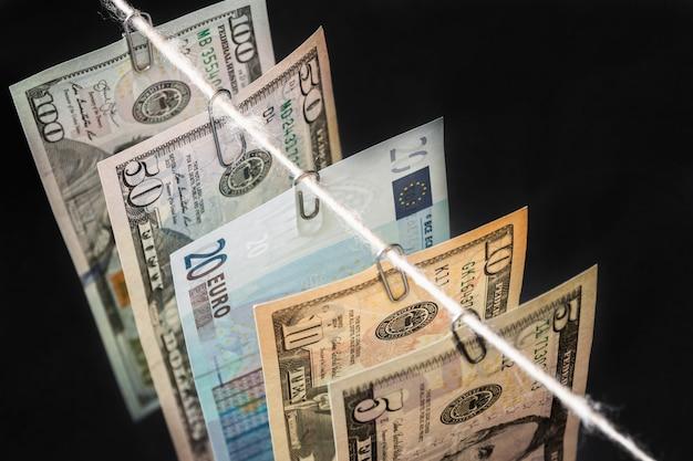 Diferentes novas notas de dólar com nota de vinte euros entre eles estão penduradas no escuro Foto Premium