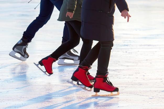 Diferentes pessoas estão patinando ativamente em uma pista de gelo. passatempos e lazer. esportes de inverno Foto Premium