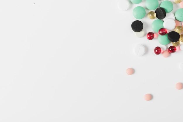 Diferentes pílulas coloridas em branco Foto gratuita