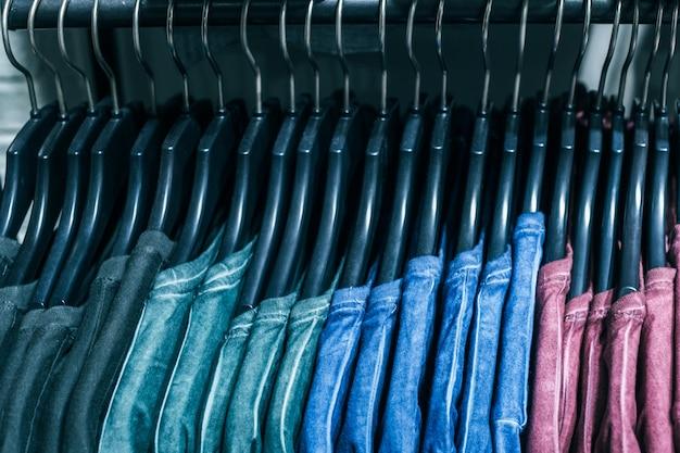 Diferentes roupas em cabides de perto Foto Premium