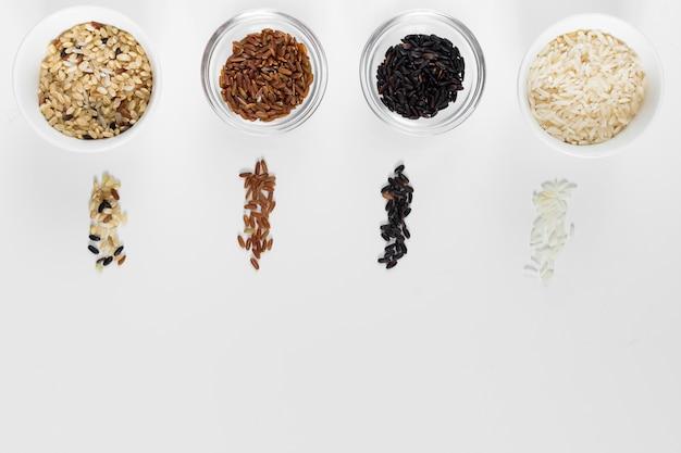 Diferentes tipos de arroz em taças na mesa de luz Foto gratuita