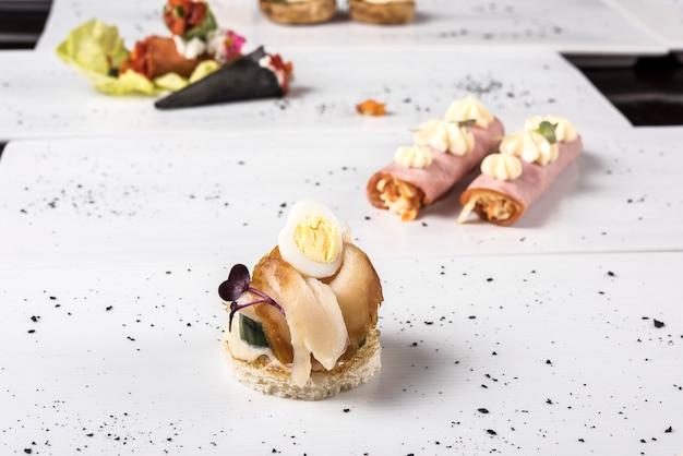 Diferentes tipos de canapés, colocados em pratos individuais, finger food, fundo escuro Foto Premium